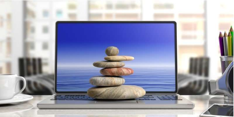 stones stacked on a laptop keyboard