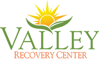 Logo for Valley Recovery Center showing sun blooming out of two leaves above the words Valley Recovery Center